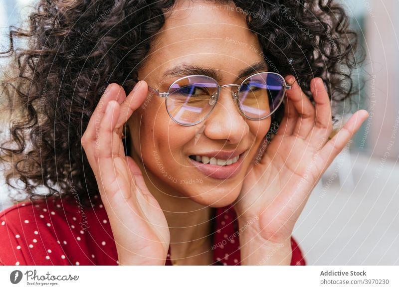 Fröhliche junge Frau mit Brille Stil trendy Mode Lächeln heiter Glück modern ethnisch ausrichten krause Haare Dame Lifestyle positiv Spektakel Inhalt Vorschein