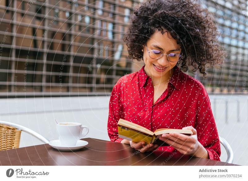 Glückliche Frau liest Buch auf der Terrasse eines Cafés lesen Kaffee ruhen genießen jung positiv ethnisch krause Haare hispanisch Brille interessant Lifestyle