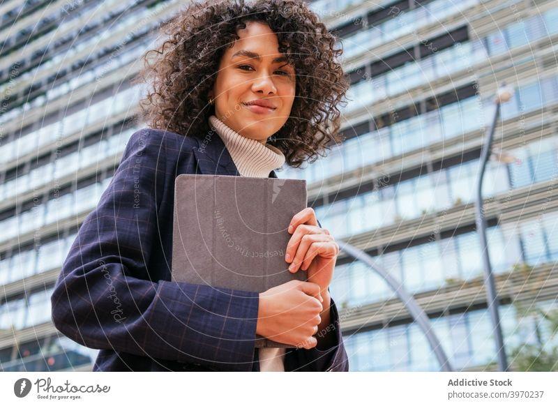 Geschäftsfrau hält Tablette auf Stadt Straße benutzend urban jung formal Browsen digital Zeitgenosse positiv ethnisch Frau krause Haare modern Lifestyle