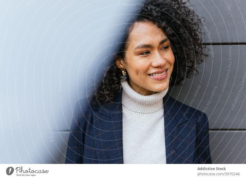 Selbstbewusste ethnische Geschäftsfrau auf der Straße stehend selbstbewusst selbstsicher Stil trendy Mode jung Frau Persönlichkeit modern Vorschein
