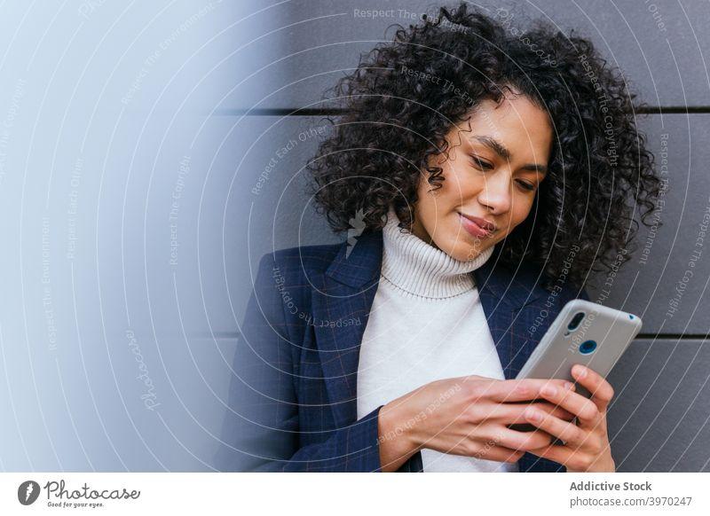 Junge ethnische Frau beim Surfen auf dem Smartphone Geschäftsfrau benutzend Browsen Mobile Telefon Apparatur jung Kommunizieren online lesen positiv