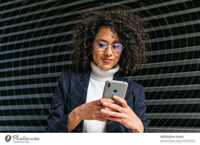 Stilvolle Frau mit Brille, die ein Smartphone aufnimmt trendy Handy Lächeln Glück jung ethnisch Geschäftsfrau benutzend Lifestyle Funktelefon Dame positiv