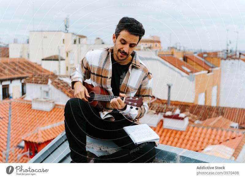 Mann mit Ukulele komponiert Musik auf dem Dach spielen Instrument komponieren Melodie Gesang akustisch Dachterrasse männlich ethnisch Gebäude Konzentration