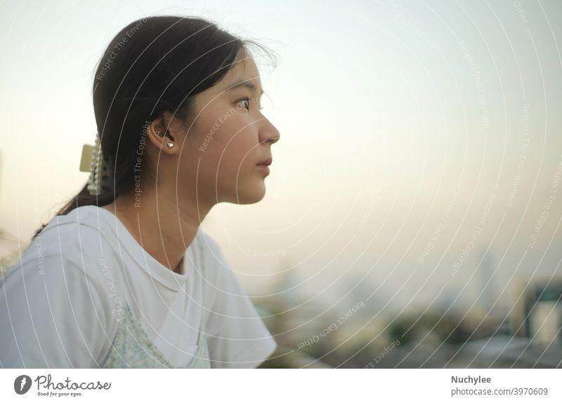 Junge asiatische Millennial Teenager-Mädchen mit Blick auf den Sonnenuntergang Himmel, emotionales Gefühl, ruhig und friedlich Hintergrund allein attraktiv