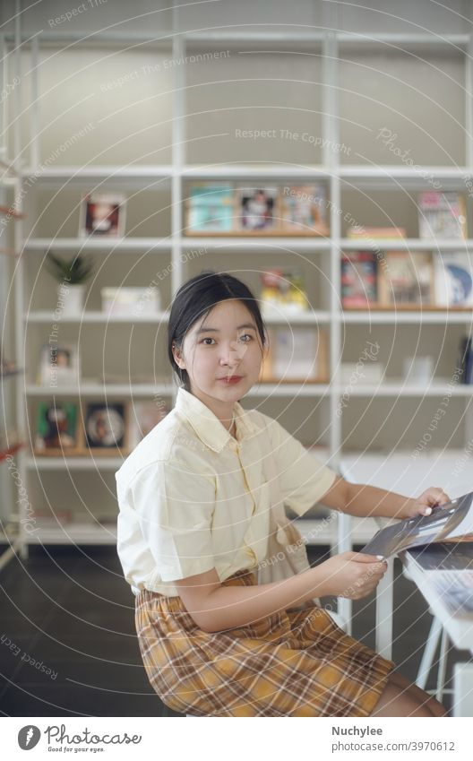 Junge asiatische Millennial Teenager-Mädchen in der modernen Bibliothek in der Schule oder Campus, Bildung und Lernen Konzept Hintergrund schön Buch brünett