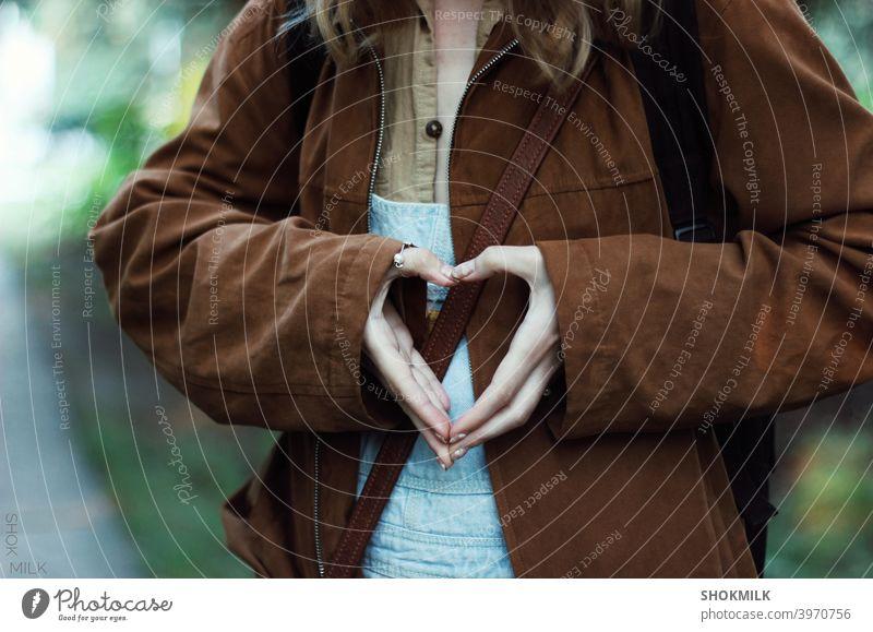 Mädchen zeigt Liebeszeichen mit ihren Fingern Zeichen Freundschaft Partnerschaft Liebeserklärung Gefühle Liebesgruß Beileid Valentinstag Romantik herzförmig
