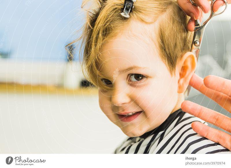 der kleine Junge in einem Friseursalon bezaubernd Baby Barbershop Schönheit blond Pflege Kaukasier Stuhl Kind Kindheit Kinder Kamm geschnitten niedlich Gesicht