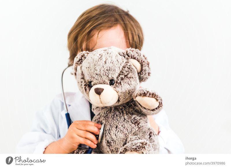 Junge als Arzt gekleidet auskultieren Teddybär auf weißem Hintergrund bezaubernd Auskultieren Baby Bär Pflege heiter Kind Kindheit Klinik Kleidung Konzepte