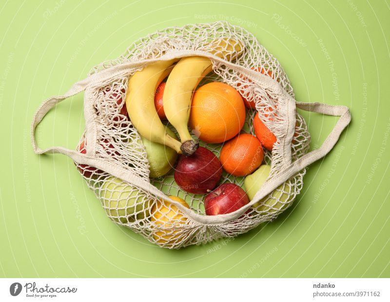 reifen frischen Früchten in einem Textil-String Tasche auf einem grünen Hintergrund, Ansicht von oben Top ineinander greifen Gesundheit natürlich