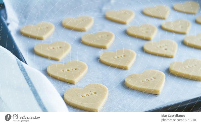 Herzförmige Kekse mit dem Wort LIEBE bereit zum Backen. Gebäck-Konzept. Valentinsgruß Geschenk heiter Datierung Cookies Valentinstag Liebe Briefe roh Backblech
