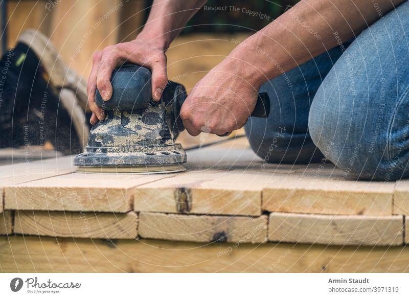 Nahaufnahme eines Arbeiters, der Holzbretter mit einer Schleifmaschine schleift Maschine Schleifen Bretter Knie Hand Arme arbeiten Staubwischen Werkzeug Gerät