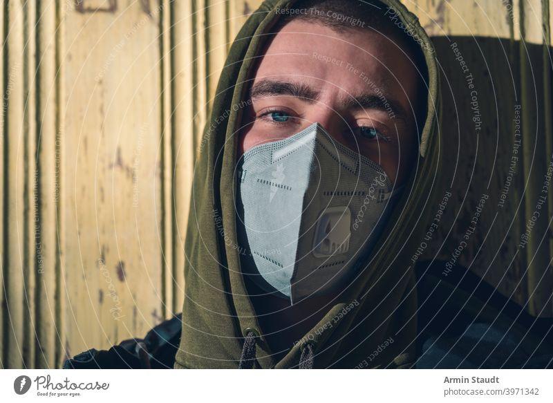 Porträt eines jungen Mannes mit einer FFP3-Koronamaske Mundschutz ffp3 Schutz Pandemie Verschmutzung Virus Gesundheitswesen Krankheit Infektion schützend