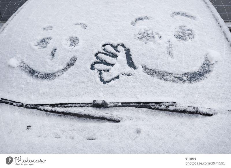 zwei Gesichter und eine Hand sind auf der Frontscheibe eines verschneiten Autos zu sehen / Winterspaß Schnee Scheibenwischer malen freikratzen zugeschneit weiß