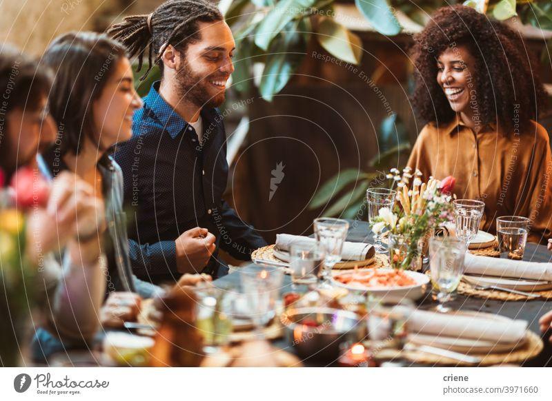 glückliche Gruppe von Freunden sitzen am Tisch beim Abendessen zusammen Erwachsener offen im Freien junger Erwachsener Alkohol Hinterhof zu feiern plaudernd