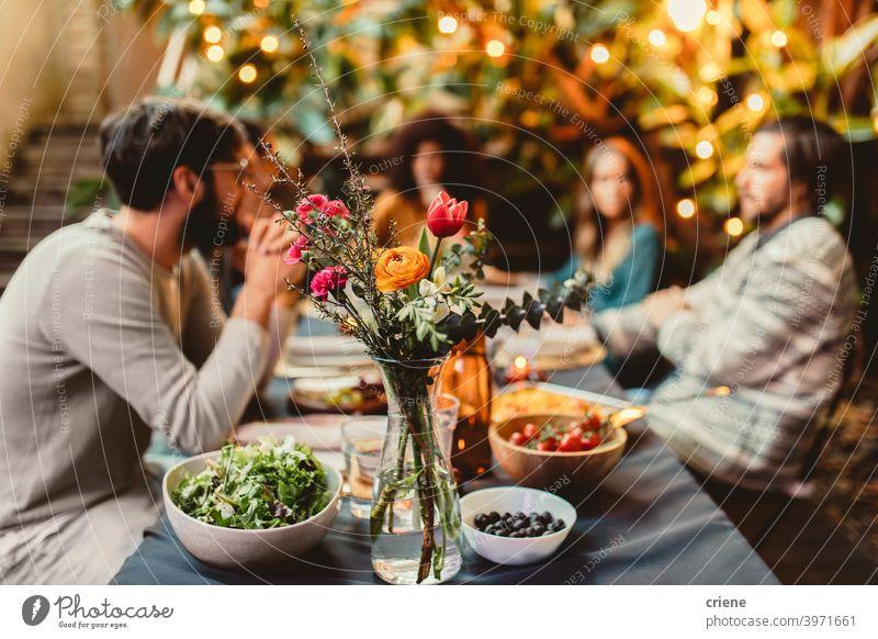 Freunde am Esstisch mit Blumen und Essen Erwachsener offen im Freien junger Erwachsener Alkohol Hinterhof zu feiern plaudernd Abendessen Dinnerparty Vielfalt