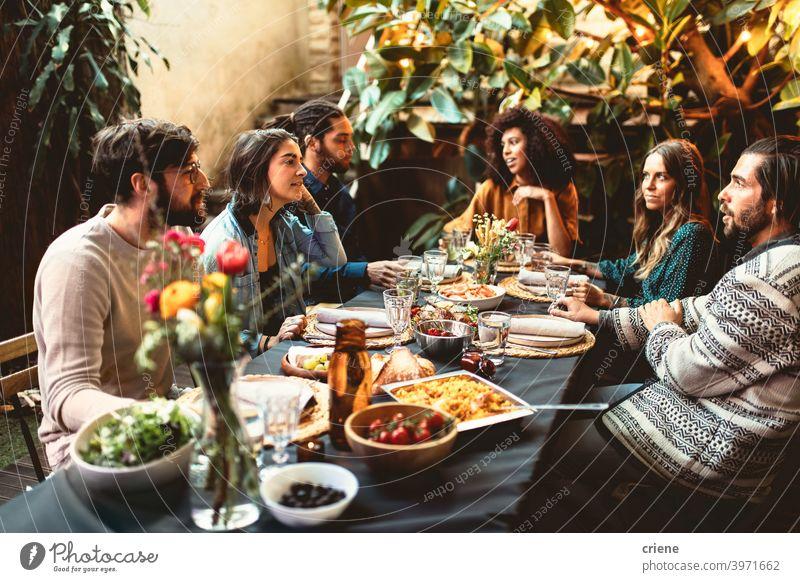 Gruppe von erwachsenen Freunden beim Abendessen Gartenparty zusammen beim Abendessen Erwachsener offen im Freien junger Erwachsener Alkohol Hinterhof zu feiern