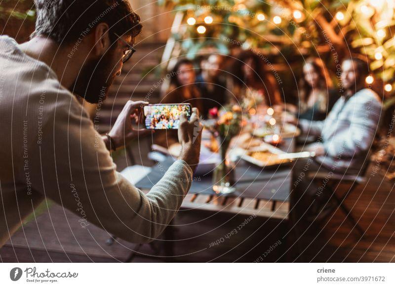junger Erwachsener, der seine Freunde mit dem Telefon bei einer Dinnerparty fotografiert offen im Freien Smartphone Alkohol Hinterhof zu feiern plaudernd