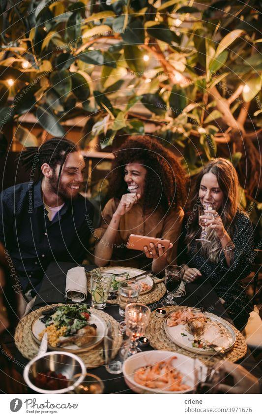 Diverse Gruppe von Freunden lachen und Spaß haben mit Telefon im Garten Abendessen Partei offen Fröhlichkeit Smartphone Lächeln junger Erwachsener