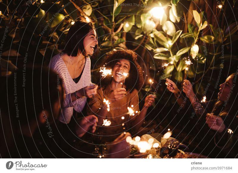 Gruppe von Freunden feiern mit Wunderkerzen bei Gartenparty zusammen 4. Juli offen Fröhlichkeit Menschen Lächeln junger Erwachsener