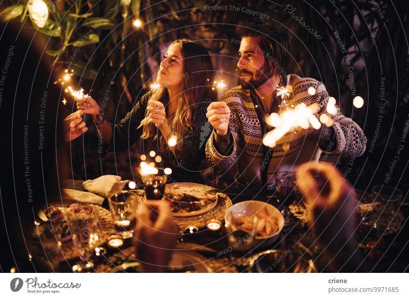 Junges erwachsenes Paar feiert mit Wunderkerzen auf einer gemeinsamen Dinnerparty 4. Juli offen Datierung Fröhlichkeit Heterosexuelles Paar Menschen Lächeln
