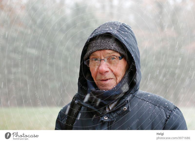 Porträt eines Seniors, der mit Winterjacke, Schal, Mütze und Kapuze im Schneegestöber steht Mensch Mann Gesicht Brille Schneefall Kälte Blick frieren draußen