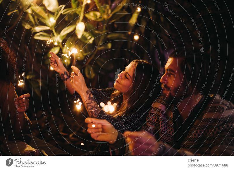 Erwachsenes Paar jubelt mit Wunderkerzen in der Nacht 4. Juli offen Datierung Fröhlichkeit Heterosexuelles Paar Menschen Lächeln junger Erwachsener Zuneigung