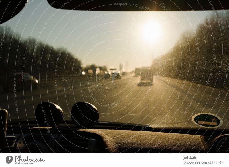 Durch die dreckige Frontscheibe eines Autos sieht man die Autobahn und die blendende Sonne fahren unterwegs mobil Mobilität Roadtrip PKW Straße Verkehr