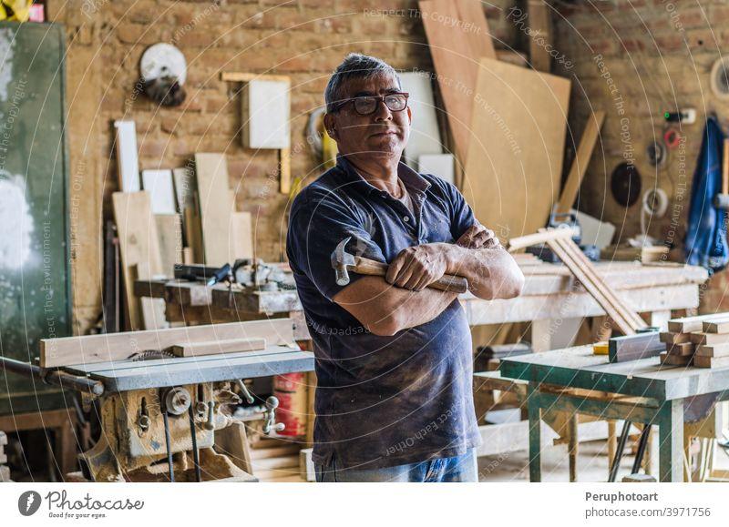 Porträt eines älteren Schreiners in seiner Werkstatt und mit Blick in die Kamera. Zimmerer Senior Schreinerei Kunsthandwerker männlich Beruf Menschen arbeiten