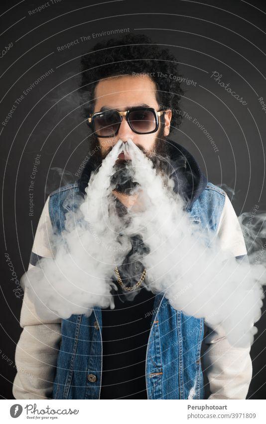 Junger Mann vaping, Studioaufnahme. Bärtiger Mann mit Sonnenbrille bläst eine Rauchwolke auf schwarzem Hintergrund. Konzept des Rauchens und Dampf ohne Nikotin.