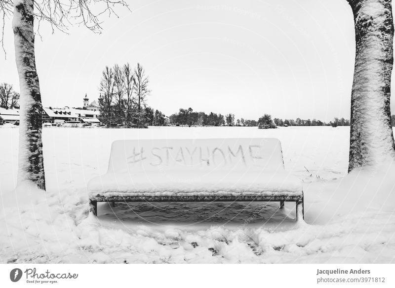 Bank im Schnee mit Hashtag Stay home stayhome Bleibt zuhause Bleibt daheim stay home Schrift Landschaft Bäume stay at home zuhause bleiben Quarantäne Schützen