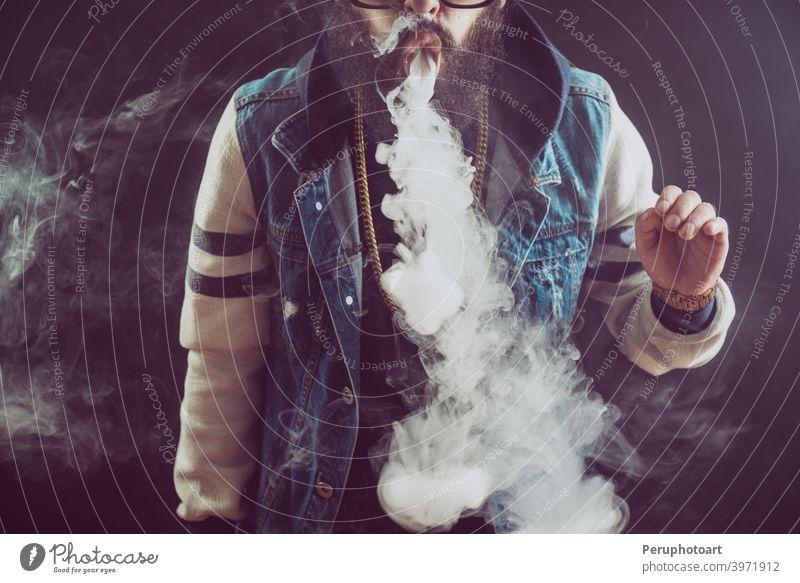 Junger Mann mit Bart, der eine Dampfwolke wirft. Schwarzer Hintergrund. Vaping eine elektronische Zigarette Raps vaping Rauch Erwachsener Cloud cool Lifestyle
