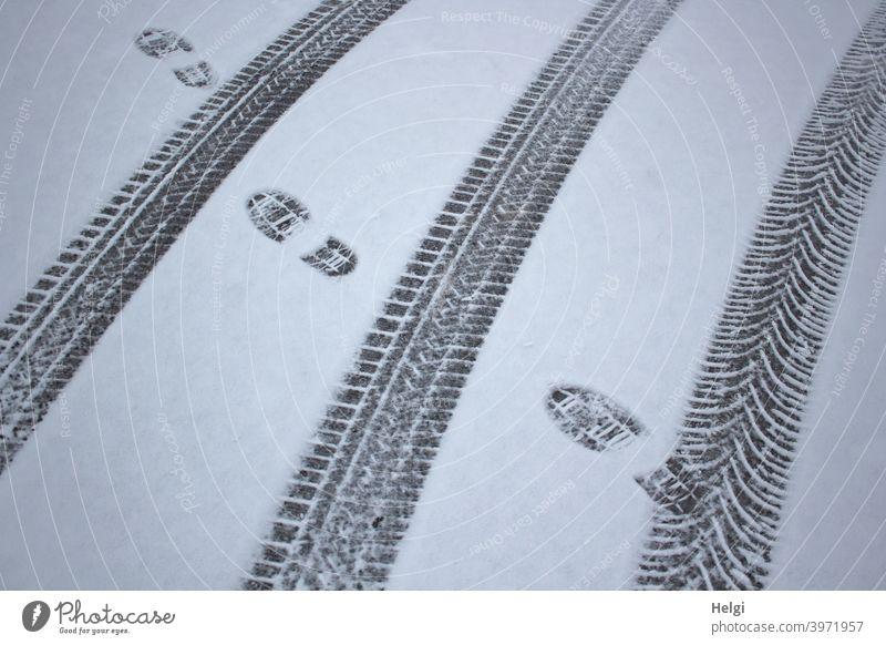 Spuren im Schnee von Autoreifen und Schuhen Winter Kälte Reifenspuren Fußspuren Abdruck Muster Struktur kalt Außenaufnahme Menschenleer weiß Schneespur Straße