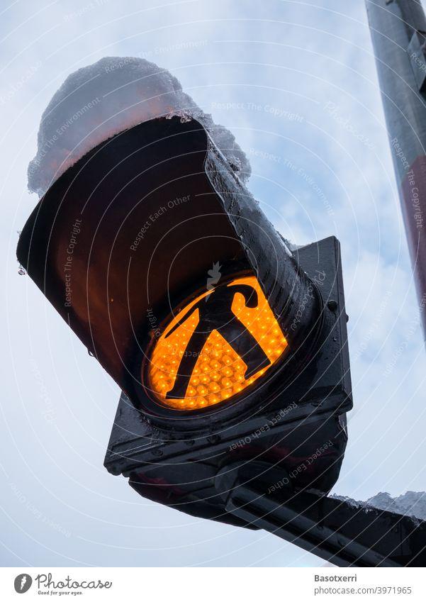 Verschneites gelbes Blinklicht mit Ampelmann am Fußgängerübergang Fußweg niemand Menschenleer Nahaufnahme Außenaufnahme Schnee verschneit schwarz von unten