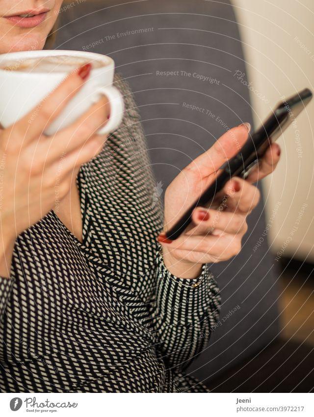 Junge hübsche Frau sitzt in einem Café, trinkt einen Cappuccino und blickt auf ihr Smartphone hübsche frau blicken Blick checken E-Mail Telefon eingeben Surfen