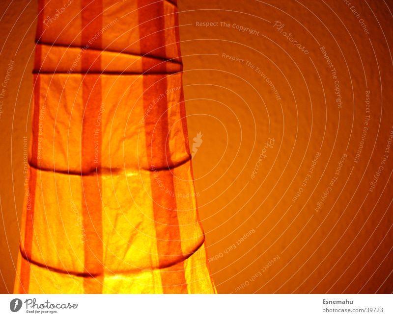Orangene Lampe Licht Stoff Papier Wand weiß dunkel Streifen vertikal horizontal Häusliches Leben orange hell Lichterscheinung Schatten