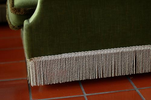 Vintage sofa aus moosgrünem samt mit Fransen steht auf Fließen in Terrakotta. Gemütlichkeit, altmodisch, vergangenheit Sofa gemütlich vintage nachhaltigkeit