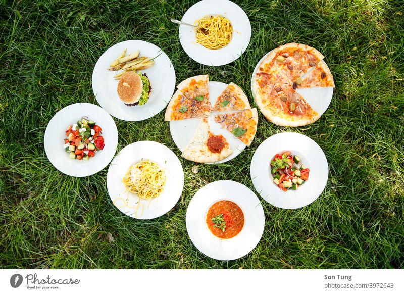 Weiße Teller mit Lebensmitteln auf Gras bei Sommerwetter Frau genießen Wetter Salatbeilage Gesundheit Party Camping Menschengruppe Burger Pizza Suppe Nudeln