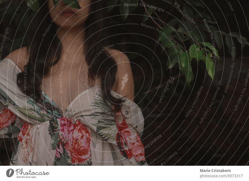 Eine Frau trägt ein Off-Shoulder-Blumenkleid gegen eine dunkle und stimmungsvolle tropische Laub Hintergrund künstlerisch Frühling Frische Konzept Wellness Ruhe