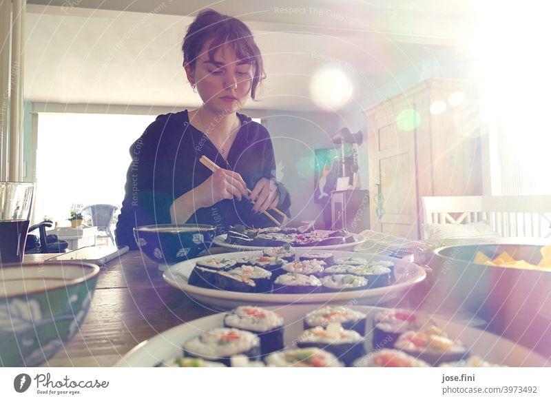 Junge Frau sitzt mit Essstäbchen an einem Tisch mit Sushi. junger Erwachsener Teenager Schüler Lifestyle Person selbstgemacht Lebensmittel Food-Fotografie