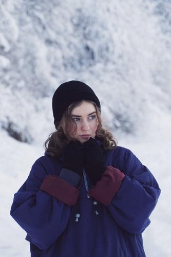 Junge Frau mit warmer Kleidung, im Hintergrund Schnee. eine Person junger Erwachsener Mädchen Jugendliche feminin Porträt hübsch frisch natürlich authentisch