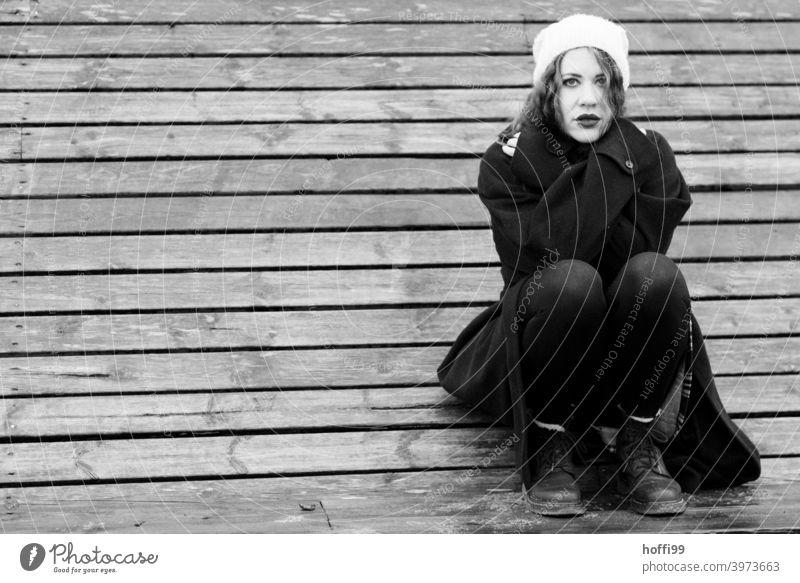 die junge Frau hockt auf einer Bank und blickt in die Kamera verschränkte Arme Mantel Blick in die Kamera langer Mantel Porträt Lifestyle authentisch hübsch