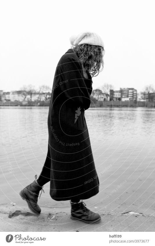 die Frau geht nachdenklich in sich gekehrt am Fluss entlang Porträt langes Haar Melancholie Jugendliche portraite 1 feminin natürlich Wegsehen Haarsträhne