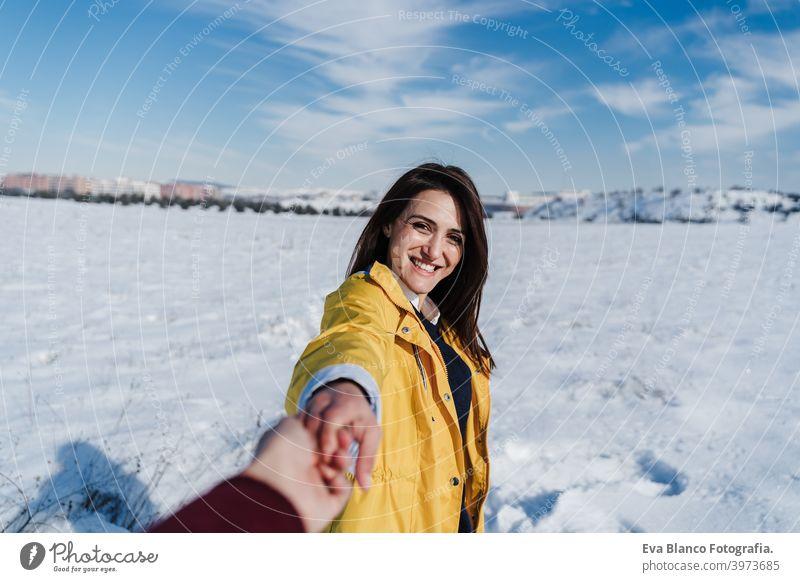 glückliche junge Frau hält Hände mit Kamera. Schnee Berglandschaft. Folgen Sie mir. Liebe und Lebensstil in der Natur Berge u. Gebirge Beteiligung Freund
