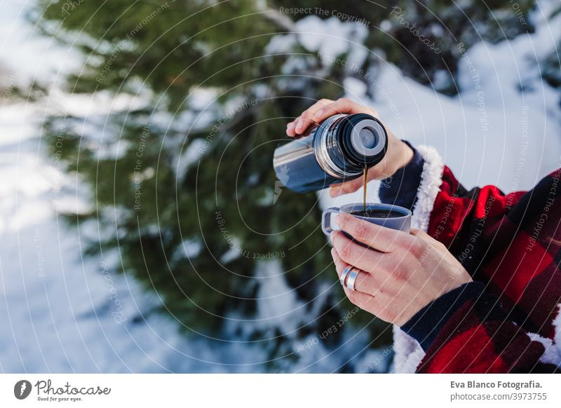 unerkennbar schöne junge Frau bei Sonnenuntergang in verschneiten Berg gießen heißen Tee aus Thermoskanne zu metallischen Tasse. Reisen und Natur Konzept. Wintersaison