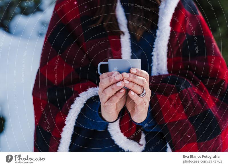 schöne Frau in karierte Decke gewickelt hält eine Tasse heißen Kaffee. Natur und Lifestyle Schnee Berge u. Gebirge Plaid heißer Tee Thermoskanne trinken sonnig