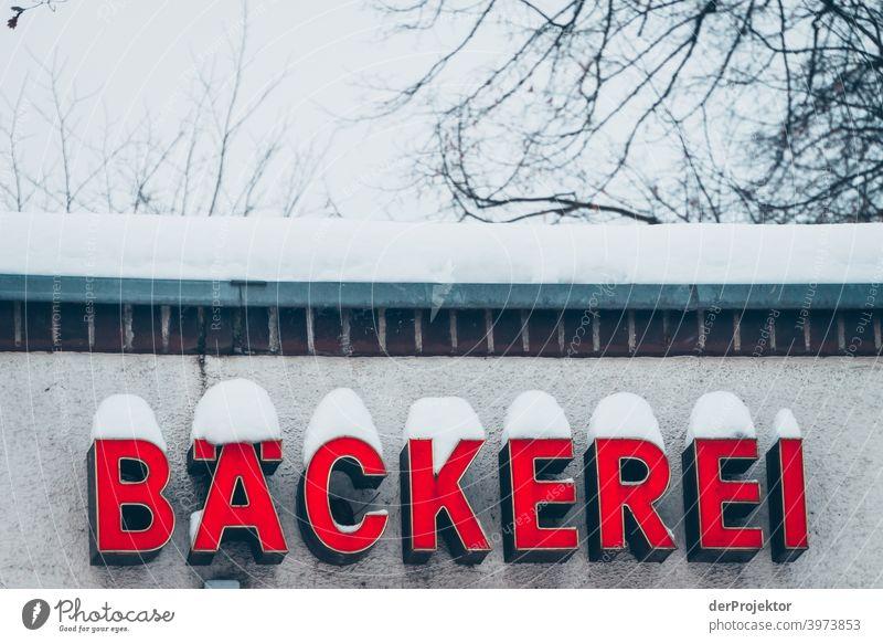 Bäckereischild mit Schnee bedeckt Winterstimmung Winterurlaub ästhetisch außergewöhnlich Textfreiraum Mitte Sonnenlicht Textfreiraum unten Textfreiraum oben