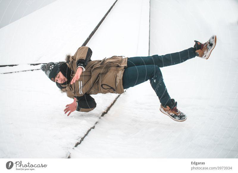Mann rutscht auf Eis aus und fällt hin Ausrutschen und Sturz Ausrutschen auf Eis Rutschgefahr rutschig ausrutschen ausgerutscht fallen fallend Winter Schnee