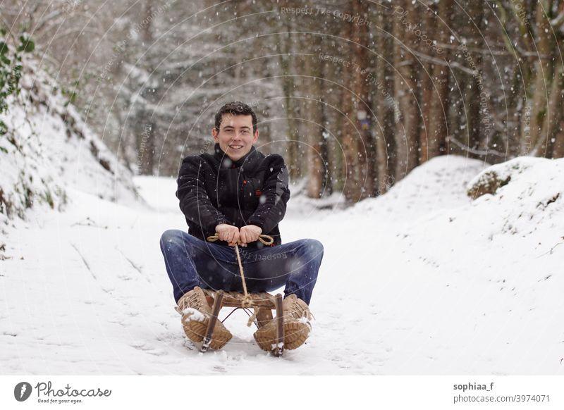 Mann fährt auf einem Schlitten, hat Spaß und lacht - Winterzeit & Schlittenspaß Rodel Schnee Reiten Lachen Fröhlichkeit Erwachsener Kindheit Rodeln Glück Freude