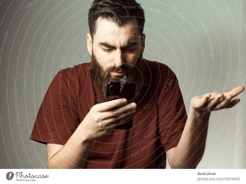 Ein junger Mann im Hipster-Stil mit Bart und modernem Haarschnitt wütend, während er auf seinen Telefonbildschirm mit Kopierraum schaut Angst verwirrt Fehler