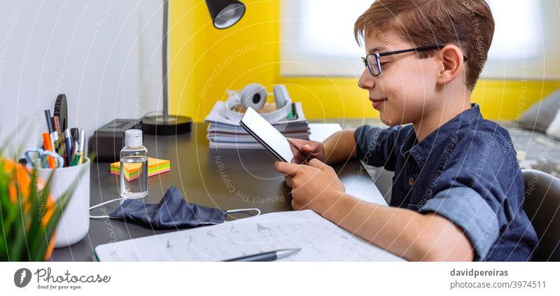 Teenager macht Hausaufgaben mit einem Tablet Blick Tablette Lächeln Heimunterricht Coronavirus Flasche für Handdesinfektionsmittel Maske auf dem Schreibtisch